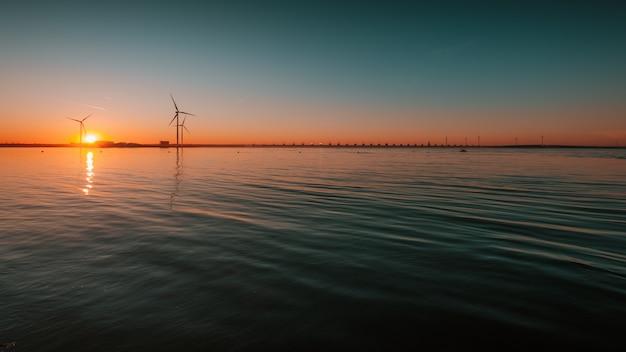 Bela vista do oceano calmo com turbinas sob o pôr do sol hipnotizante no Foto gratuita