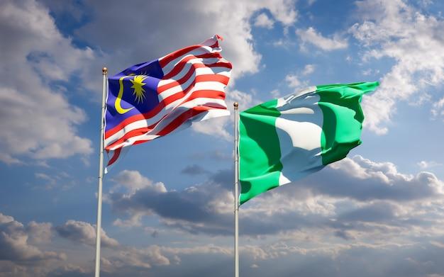 Belas bandeiras estaduais da malásia e da nigéria juntas no céu azul Foto Premium