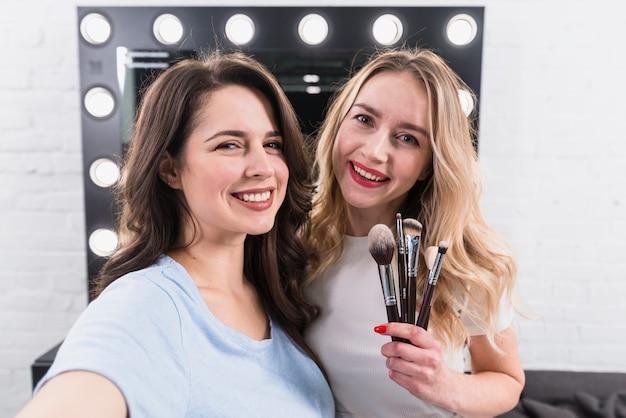 Belas mulheres sorridentes com escovas tomando selfie Foto gratuita