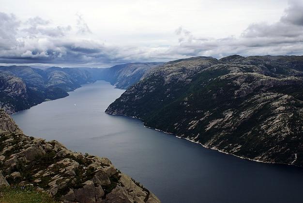 Belas paisagens das famosas falésias preikestolen perto de um lago sob um céu nublado em stavanger, noruega Foto gratuita