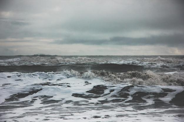 Belas paisagens das ondas do oceano forte incrível durante o tempo enevoado no campo Foto gratuita