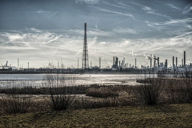 Belas paisagens de edifícios industriais na costa, cercada por grama sob céu de tirar o fôlego Foto gratuita