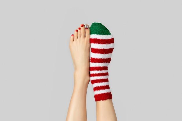 Belas pernas de mulher com design de unhas de natal e meias Foto Premium