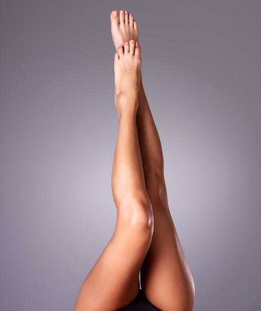 Belas pernas femininas após a depilação. foto em fundo cinza Foto gratuita
