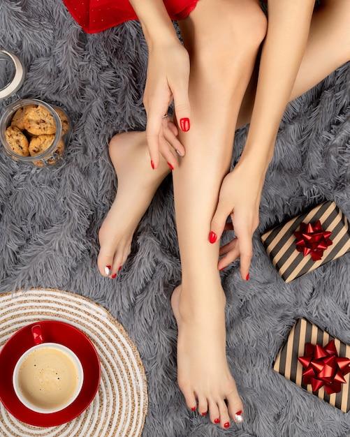 Belas pernas femininas com desenho de unhas de natal no tapete cinza fofinho Foto Premium