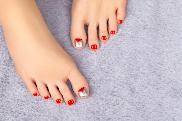 Belas pernas femininas com desenho de unhas no tapete cinza fofinho Foto Premium