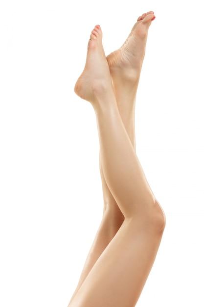 Belas pernas femininas isoladas no branco. Foto gratuita