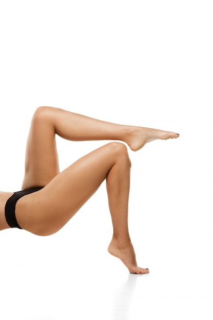 Belas pernas femininas isoladas no branco Foto gratuita