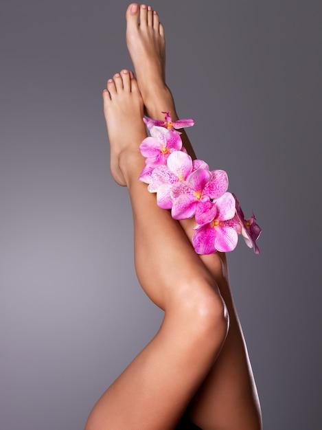 Belas pernas longas femininas com flor. conceito de tratamento de beleza Foto gratuita