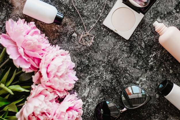 Beleza apartamento leigos com acessórios, perfumes, cosméticos e peônias em um fundo de mármore escuro Foto Premium