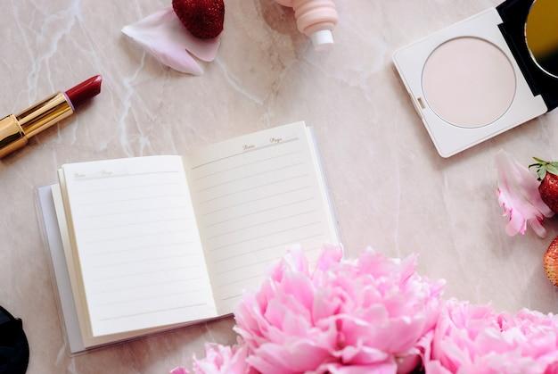 Beleza apartamento leigos com um diário, smartphone, acessórios e peônias em um fundo de mármore Foto Premium