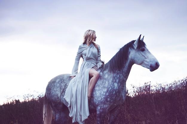 Beleza blondie com cavalo no campo, efeito de tonificação Foto Premium