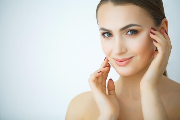Beleza cuidados com a pele. mulher bonita, aplicar creme cosmético para o rosto Foto Premium