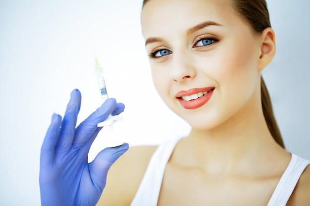 Beleza e cuidado. retrato de uma jovem mulher com uma pele bonita. cosmetologia. mulher com lindos olhos azuis. injeção de cosmetologia. injecção juvenil Foto Premium