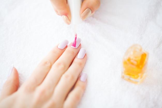 Beleza e cuidados. manicure mestre aplicando esmalte no salão de beleza. mãos de mulheres bonitas com manicure perfeita. spa manicure Foto Premium