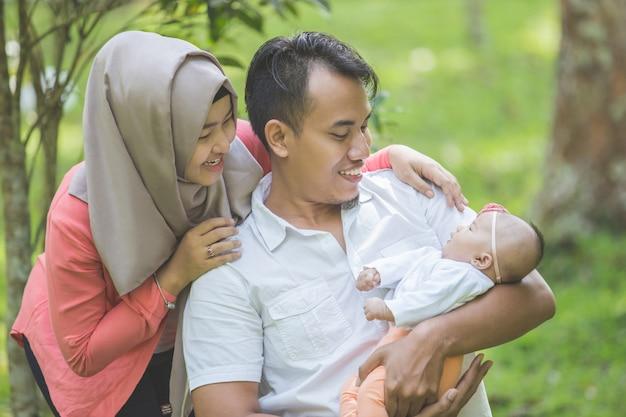 Beleza mãe e pai com seu bebê recém-nascido no parque Foto Premium