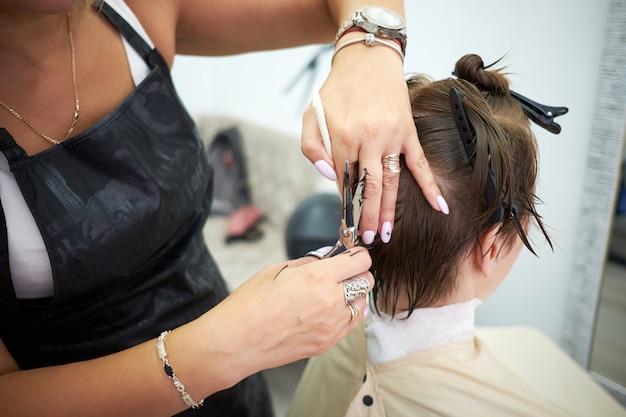 Beleza, penteado, tratamento, conceito de cuidados do cabelo. jovem mulher elegante no salão de cabeleireiro. cliente de serviço de cabeleireiro na barbearia ou salão de beleza. Foto Premium