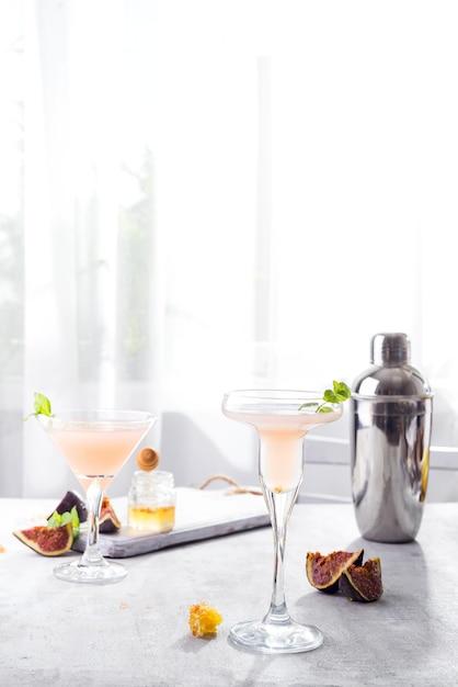Bellini coquetel com pêssego e figos, mel na luz de fundo sobre windows Foto Premium
