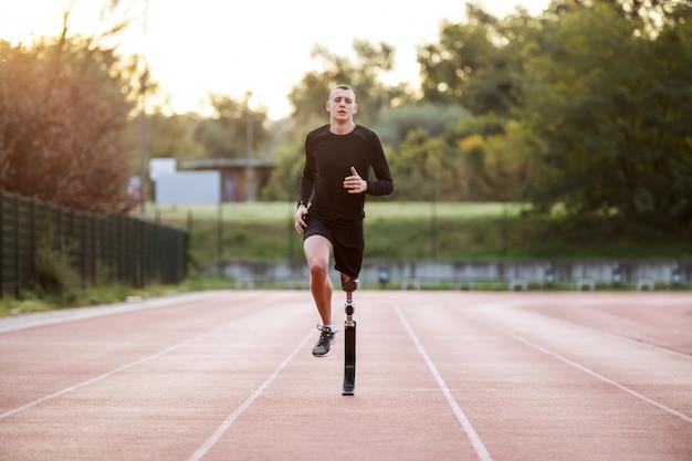 Belo apto desportivo caucasiano jovem deficiente em roupas esportivas e com perna artificial correndo na pista de corrida no estádio. Foto Premium