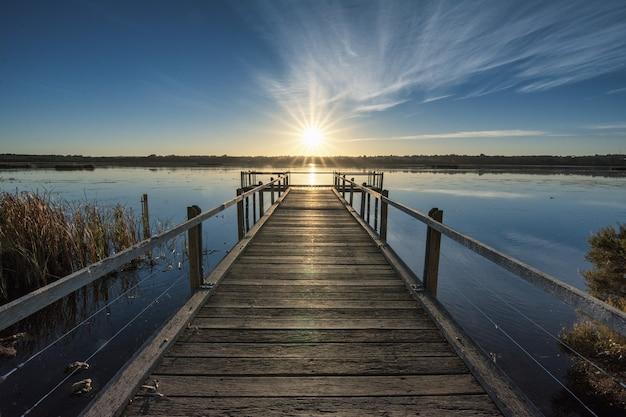 Belo cais de madeira à beira do oceano calmo com um belo pôr do sol no horizonte Foto gratuita