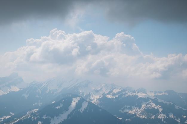 Belo cenário de nuvens brancas cobrindo a cadeia de altas montanhas rochosas Foto gratuita