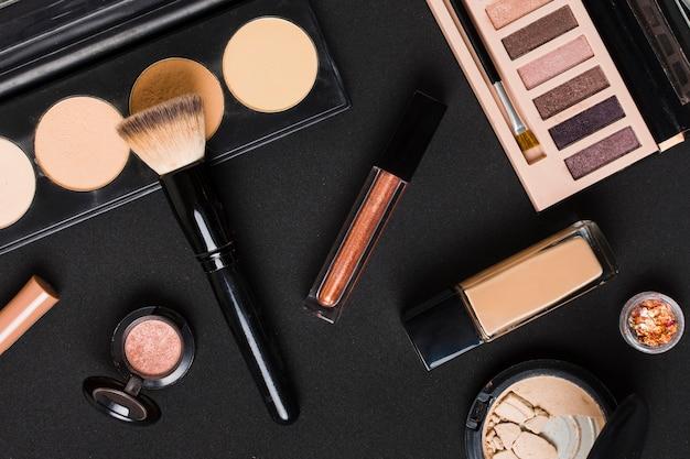 Belo conjunto de cosméticos maquiagem profissional na mesa escura Foto gratuita