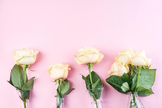 Belo corte fresco bege rosas em vaso de vidro no fundo rosa Foto Premium