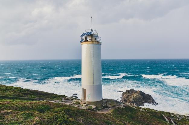 Belo farol nas falésias com o magnífico mar tempestuoso Foto gratuita