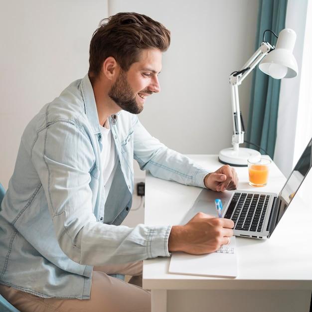 Belo homem adulto trabalhando em casa Foto gratuita