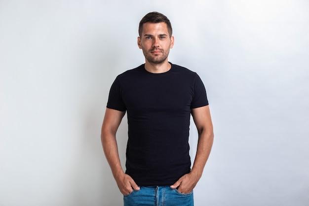 Belo homem vestindo em preto t-shirt em pé, segurando os braços no bolso, olhando seriamente para a câmera Foto Premium