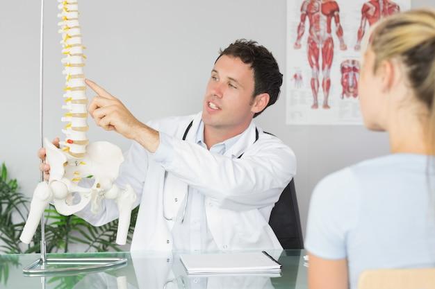 Belo médico mostrando um paciente algo no modelo de esqueleto Foto Premium