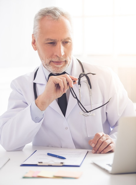 Belo médico no jaleco branco está usando um laptop. Foto Premium