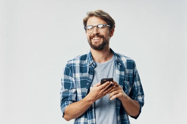 Belo modelo masculino com barba com um telefone posando no estúdio Foto Premium