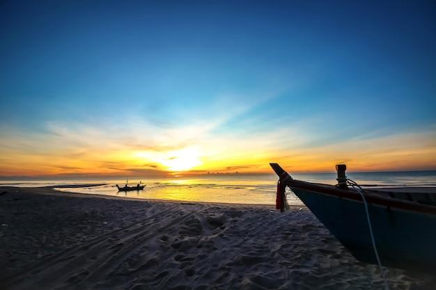 Belo nascer do sol pôr do sol na praia com barco silhueta Foto Premium