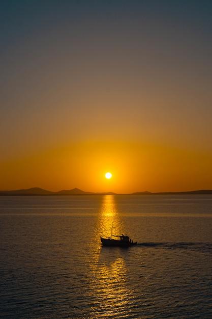 Belo oceano com um pequeno barco flutuando na água ao pôr do sol Foto gratuita