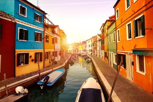Belo pôr do sol com barcos, edifícios e água. luz solar. toning. burano, itália. Foto gratuita