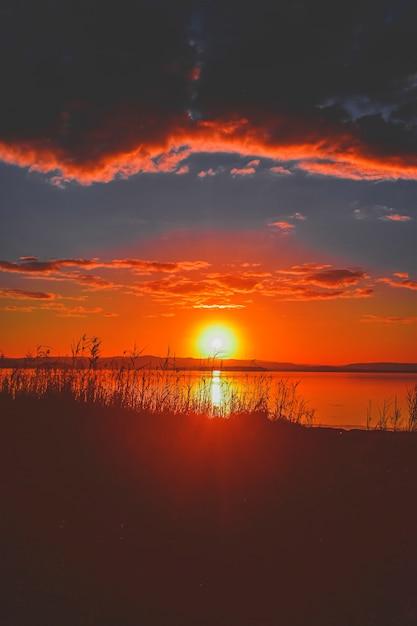 Belo pôr do sol no lago com vegetação na costa e incrível céu nublado Foto gratuita