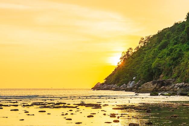 Belo pôr do sol sobre a montanha ao redor da praia, mar, oceano e rocha Foto gratuita
