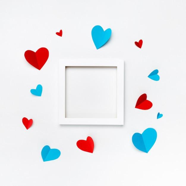 Belo quadro quadrado branco com copyspace para texto em fundo branco, decorado com corações de papel artesanal Foto gratuita