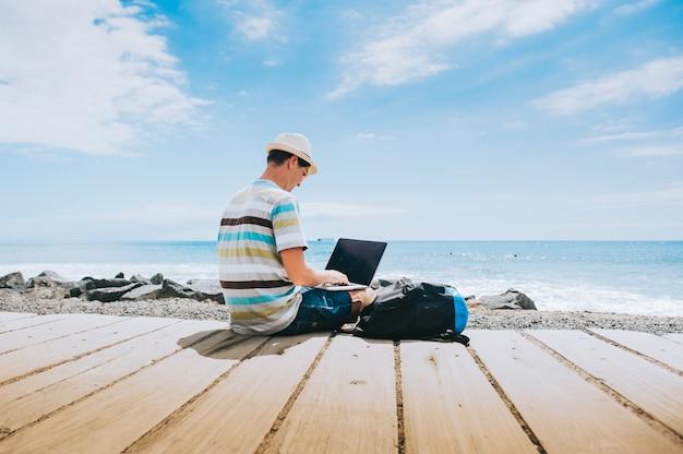 Belo rapaz o fotógrafo a trabalhar com um laptop na praia Foto Premium
