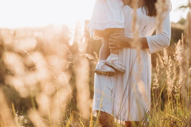 Belo retrato de mãe encantadora e adorável filhinha atravessar o campo Foto gratuita