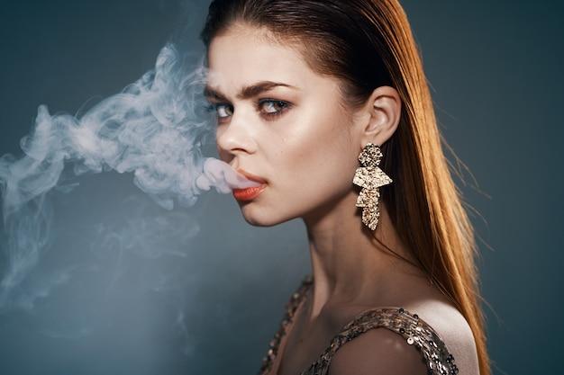 Belo retrato de uma mulher de beleza com vapor da boca Foto Premium