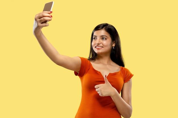 Belo retrato feminino de meio comprimento isolado. jovem mulher indiana emocional em vestido fazendo selfie. espaço negativo. expressão facial, conceito de emoções humanas. Foto gratuita