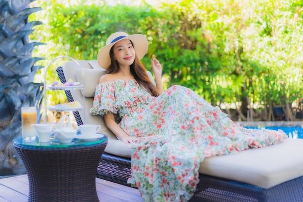 Belo retrato jovem mulher asiática com jogo de chá da tarde com café sentar na cadeira ao redor da piscina Foto gratuita