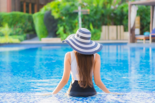 Belo retrato jovem mulher asiática sorriso feliz relaxar ao redor da piscina no hotel resort Foto gratuita