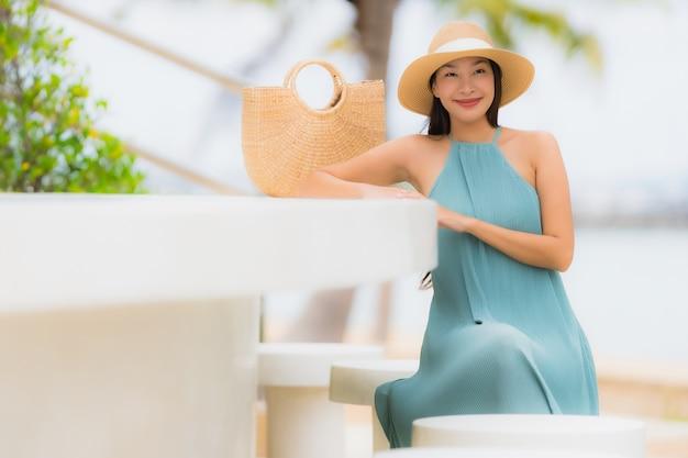 Belo retrato jovem mulheres asiáticas sorriso feliz relaxar ao redor da praia mar oceano Foto gratuita