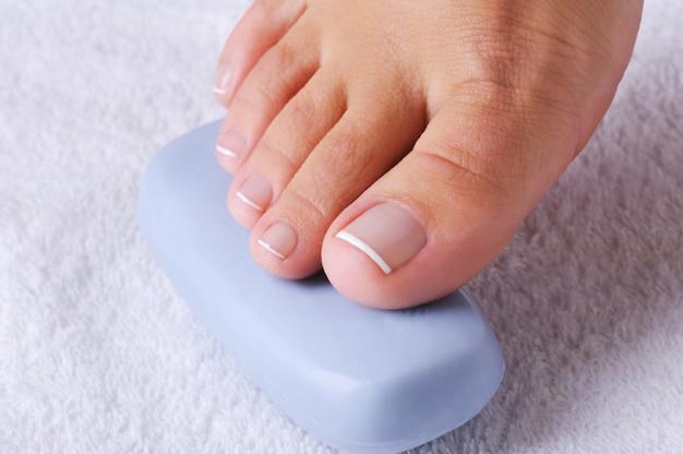 Belo único pé feminino com a bela pedicura nos dedos sobre uma fatia de sabonete azul. Foto gratuita