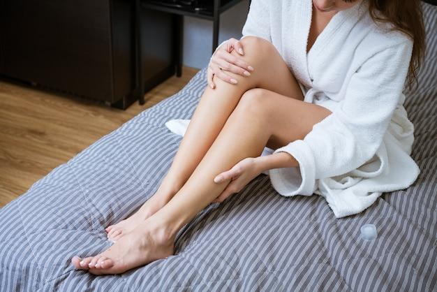 Belos pés bem tratados na cama. conceito de cuidados com a pele dos pés em casa Foto Premium