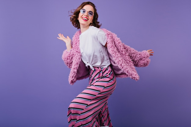 Bem-aventurada garota encaracolada em óculos de sol rindo enquanto posava em uma jaqueta de pele rosa. tiro interno de mulher jovem e bonita dançando na parede roxa com um sorriso. Foto gratuita