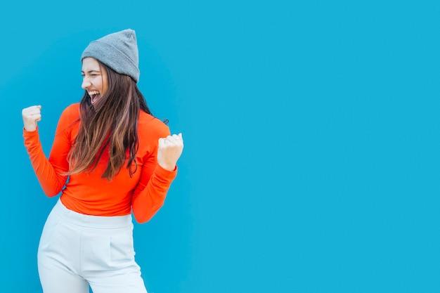 Bem sucedida jovem feliz com punhos cerrados na frente da superfície azul Foto gratuita